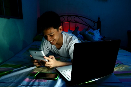 Young Teen in front of a laptop computer and on a bed and using a tablet photo