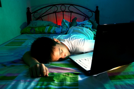 Young Teen sleeping front of a laptop computer and on a bed photo