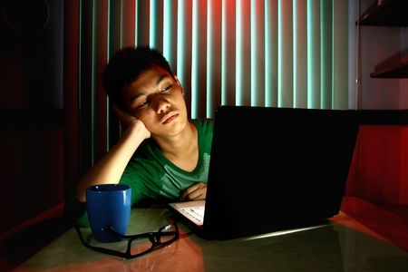 Young Teen bored in front of a laptop computer photo
