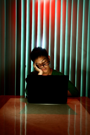Young Teen with eyeglasses sleeping in front of a laptop computer photo