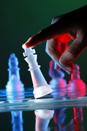 Finger tilting a chess piece on Chess Board Stock Photo