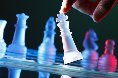 concede: Finger tilting a chess piece on Chess Board Stock Photo
