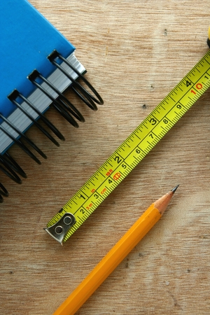wooden metre: Photo of a blue Notebook, tape measure and a pencil