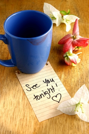 tonight: Coffee mug with lipstick mark and a note saying see you tonight Stock Photo