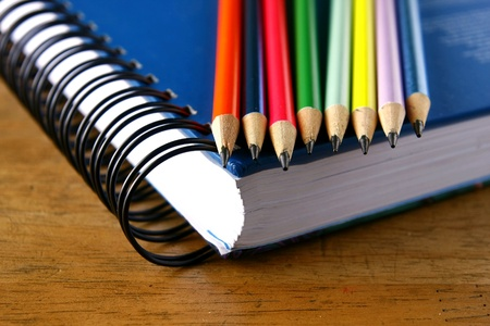 Colored Pencils and a notebook on a wooden table