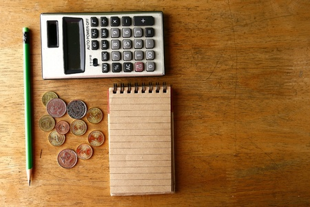 compute: Coins, pencil, notebook and calculator on a table