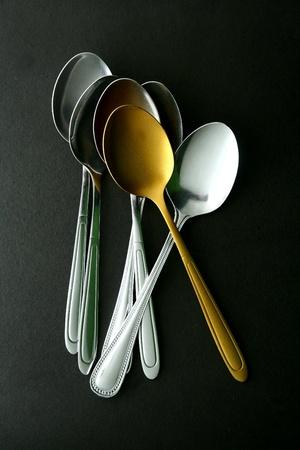 shiny metal: A single Golden spoon among silver spoons