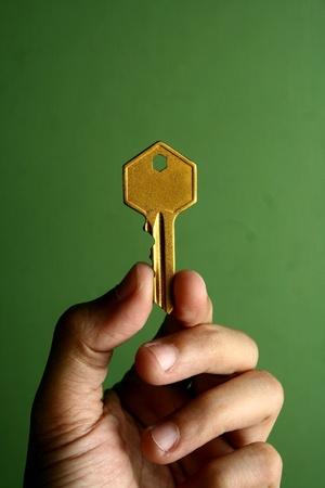 shiny metal: Hand holding a golden key