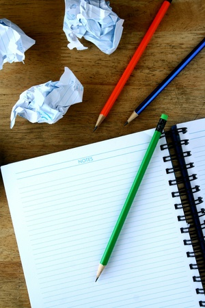 rough: Colored pencils, crumpled papers and a notebook on a wooden table