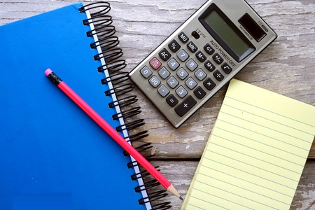art: Colored pencils, calculator, notepad and a notebook on a wooden table