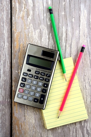 Colored pencils, calculator and a notepad and on a wooden table Stock Photo