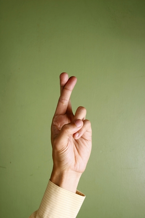 crossing fingers: Photo of a hand crossing fingers Stock Photo
