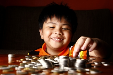 Photo of a young boy stacking or piling coins