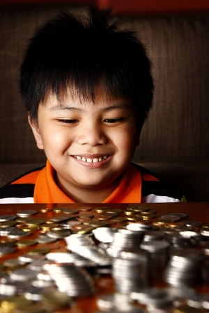 piling: Photo of a young boy stacking or piling coins