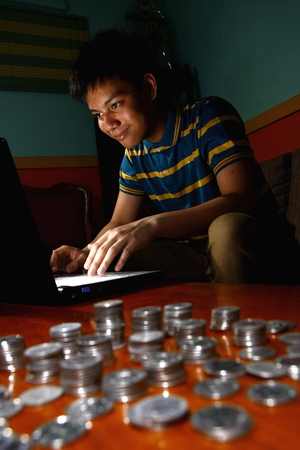 Photo of an Asian Teen in front of laptop computer and a stack of coins beside him