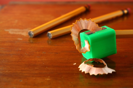pencil sharpener: Pencil in a sharpener and two unsharpened pencils