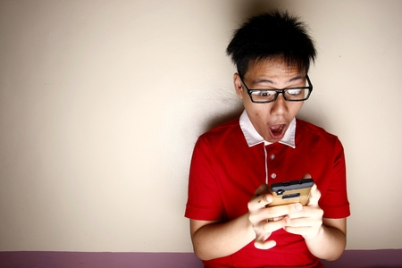 Teenage kid using a smartphone and acting surprised Stok Fotoğraf