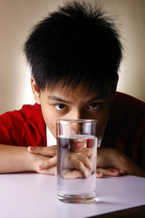 rehydration: Teen looking at a glass of water on a wooden table