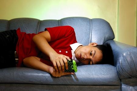 Adolescente que usa un teléfono inteligente mientras se está acostado en un sofá y sonriendo Foto de archivo