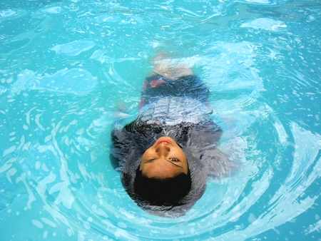 backstroke: Photo of a Teenage girl swimming backstroke in a pool