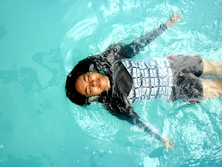 floater: Photo of a Teenage girl swimming backstroke in a pool