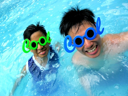 Photo of Two teenage boys wearing sunglasses with the word cool for its frame in a swimming pool