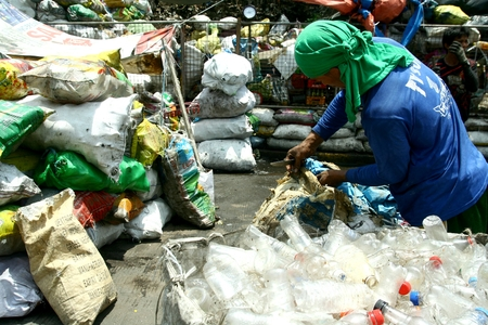 scavenge: scavenger sorting through trash at a dump site in Manila Philippines to look for recyclable things that he can sell
