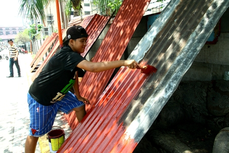 scavenge: Man repainting used G.I. roofing sheets salvaged from a dump site in Manila Philippines called Smokey Mountain