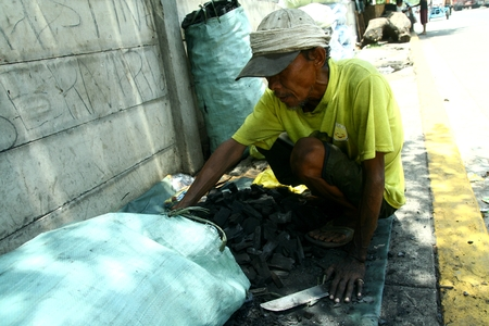 scavenge: Man packing charcoal into a sack made from salvaged wood from a dump site in Manila Philippines called Smokey Mountain Editorial