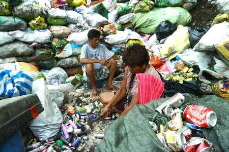 segregated: Scavengers at a dump site called Smokey Mountain in Manila Philippines prepares segregated recyclable waste products to be sold to recycling facilities