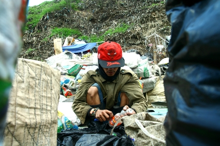 scavenger: scavenger sorting through trash at a dump site in Manila Philippines to look for recyclable things that he can sell