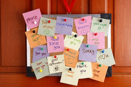 push in pins: Cork board with messages on colorful papers and push pins hanging by a door Stock Photo
