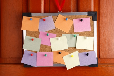 push in pins: Cork board with colorful papers and push pins hanging by a door
