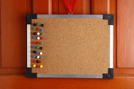 push in pins: Cork board with colorful push pins hanging by a door