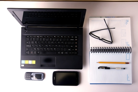 writing materials: Laptop computer cellphone smartphone notebook pen pencil and eyeglasses