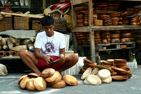 weave: Wood carver puts finishing touches on wood plates and trays in dapitan arcade, manila, philippines