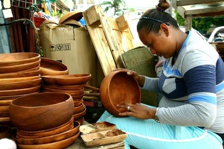 carver: Carver de madera pone los toques finales en placas de madera y las bandejas en la arcada Dapitan, Manila, Filipinas