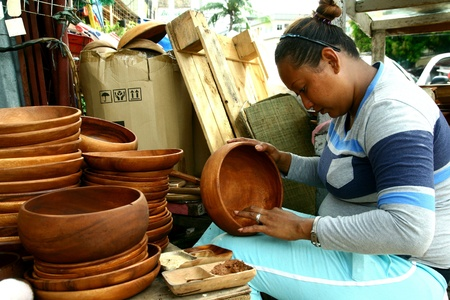 carver: Wood carver puts finishing touches on wood plates and trays in dapitan arcade, manila, philippines