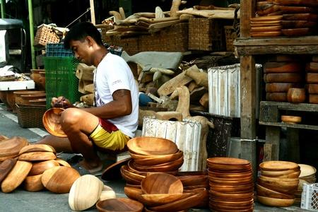 schnitzer: Holzschnitzer legt letzte Hand auf Holz Teller und Tabletts in Dapitan arcade, Manila, Philippinen