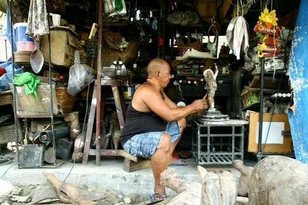 wood figurine: Carver de madera pone los toques finales en una estatuilla de madera en la arcada Dapitan, Manila, Filipinas