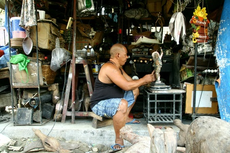 wood figurine: Wood carver puts finishing touches on a wood figurine in dapitan arcade, manila, philippines