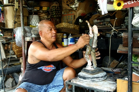 schnitzer: Holzschnitzer setzt den letzten Schliff auf einem Holz-Figur in Dapitan arcade, Manila, Philippinen