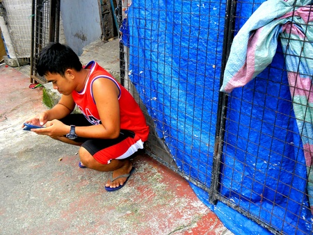 A man uses his smartphone while sitting on a sidewalk
