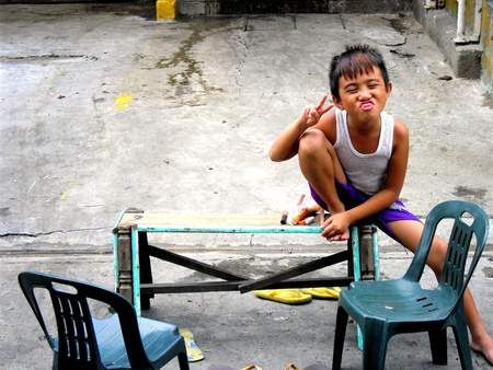 sitted: Young boy smiling and making a funny face and peace sign