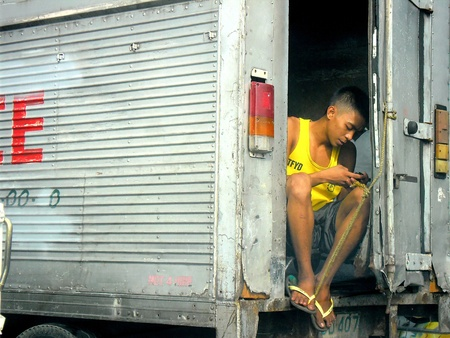 telecommunicate: Young man using a smartphone while at the back of a truck van Stock Photo