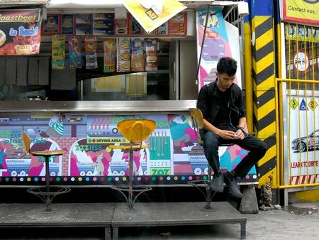 man: Man smoking a cigarette while on a hamburger stall Stock Photo