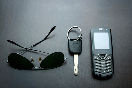 telecommunicate: Dark sunglasses, key and a cellphone on a table