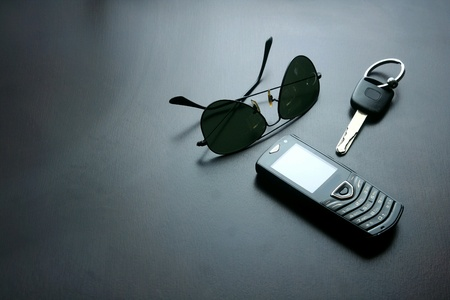 Dark sunglasses, key and a cellphone on a table