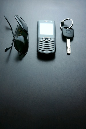 dark: Dark sunglasses, key and a cellphone on a table