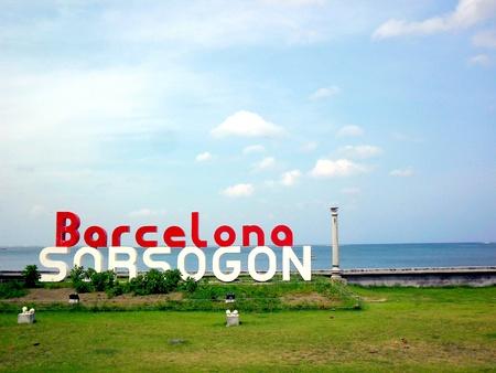 beside: Barcelona sorsogon sign at a park in a beach shore beside an old church ruins Stock Photo